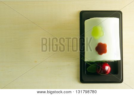 Fancy soap in cake form with cherry on the top on wooden board background