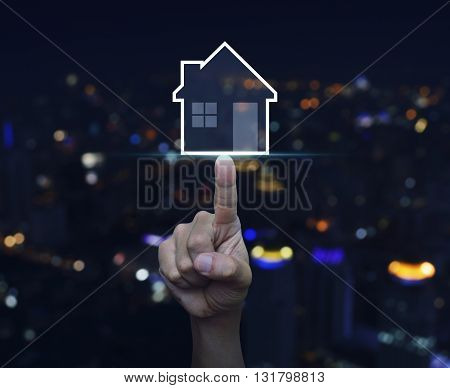Hand pressing house icon with copy space over blurred light city tower background Real estate concept