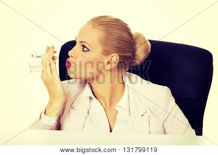 Business woman sitting behind the desk and trying to smoke a few cigarettes