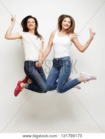 lifestyle portrait of two young hipster girls best friends jump