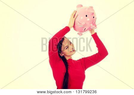 Happy young woman shaking piggybank