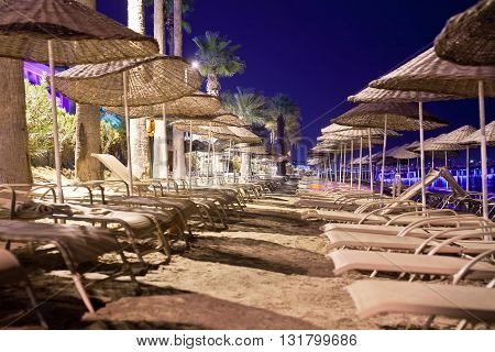 Sunbeds and umbrellas on the beach in the evening.