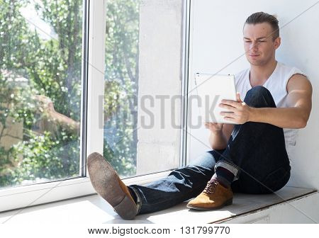 Young fashion man sitting near  window with tablet.