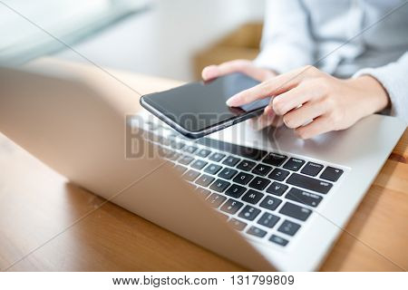 Woman hand touch phone over laptop keyboard