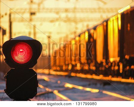 Railway traffic light at sunset shows red signal on railway. Red light. Moving train on the background.