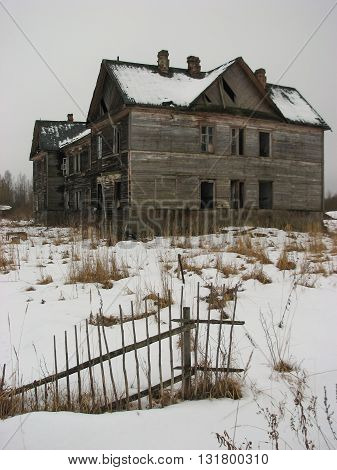 Terrible and scary abandoned house and broken old wood fence in winter period