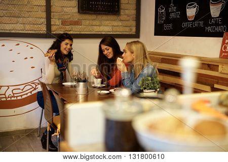 Three girls having coffee together, talking, having fun in cafe.