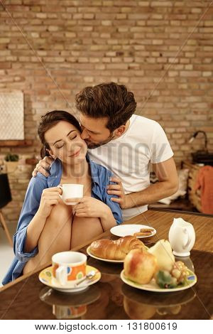 Young couple kissing in the morning at breakfast table at home.