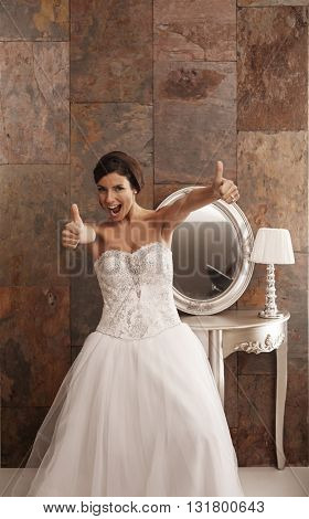 Happy bride in wedding dress showing thumbs up.