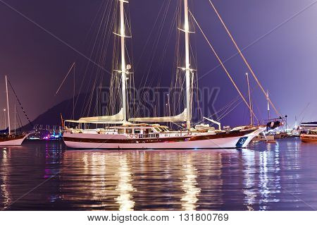 Beautiful two-masted yacht moored in the harbor in the evening.