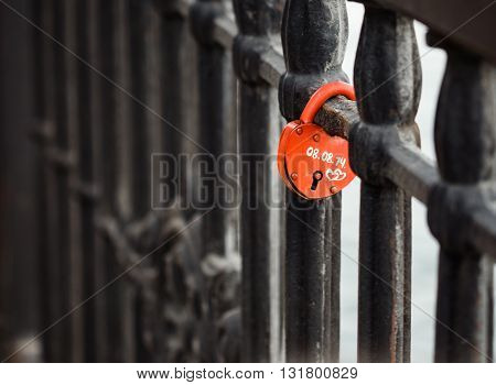 Closed red padlock in the form of heart locked on bridge