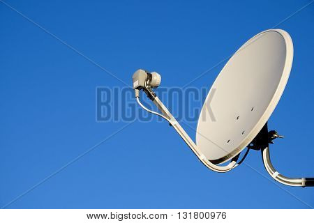 Satellite TV antenna on blue sky background