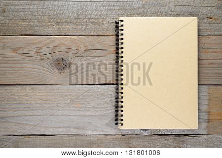 Closed notepad on wooden table top view