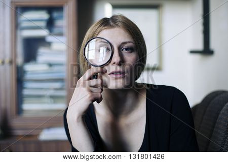 Close up portrait of a beautiful woman with a glass magnifier her eye is magnified