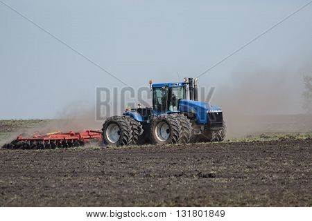 tractor with plow plowing a field .
