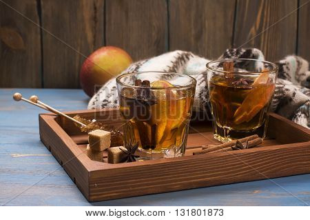 Winter drink. Warm mulled apple cider with spices: cinnamon, cloves on wooden tray