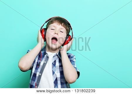 Portrait Of Young Boy With Headphones On Mint Background