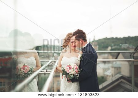 Happy wedding couple, bride, groom kissing with view of old city.