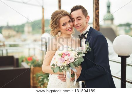 Beautiful couple, bride and groom posing on balcony with backgrounf of old city.