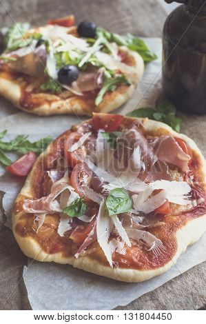 Photos of prosciutto mini pizza on rustic background