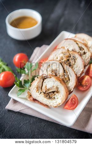 Rolled meat with champignons on rustic background