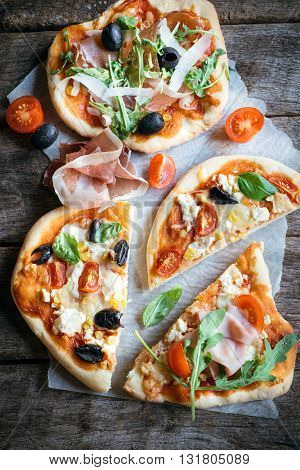 Served prosciutto mini pizza on rustic background