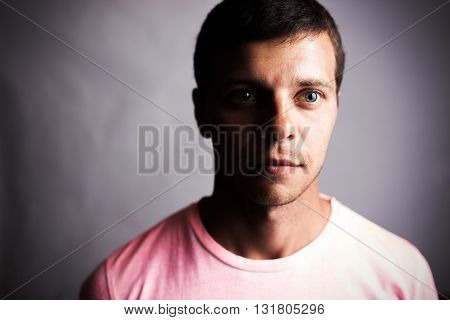 Dark portrait of a young man looking forward.