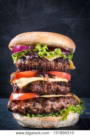Photos of triple burger on rustic background