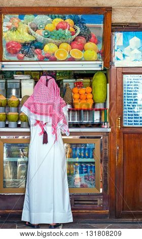 Dubai U.A.E. - February 17 2007: A man in traditional dress in front of a fruit and juice shop in the old souk