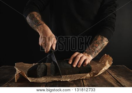 Unrecognizable Baker In Black Sweatshot With Tattooed Hands Cut Freshly Baked Homemade Charcoal Brea