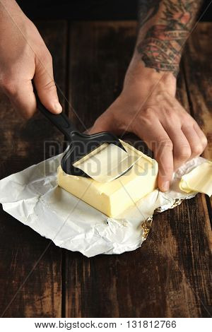 Tattooed Man Hands Use Special Knife To Chop Really Thin Slice Of Butter, Everything On Rustic Woode