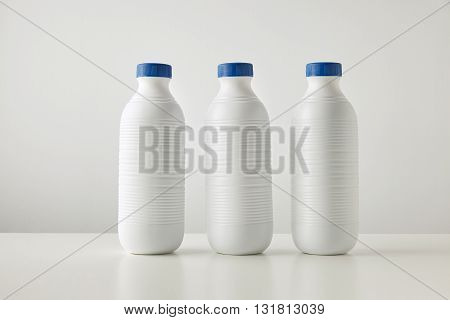 Three Blank White Plastic Riffled Bottles With Blue Caps In Row Isolated On Table In Center Space Fo