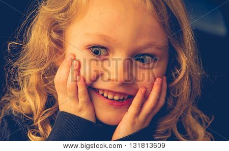 close up of a 4 year old caucasian child with blonde hair and blue eyes with chin in his hands looking surprised.