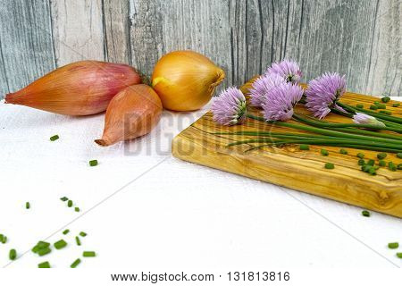 Fresh green blooming chives shallots and yellow onion on white and wooden background
