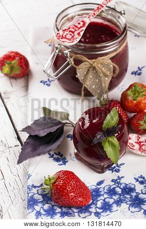 Homemade berry jam with basil leaves in a jar on white grunge wooden table