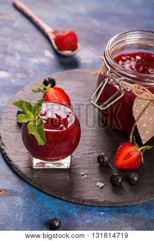 Strawberry, blueberry and raspberry jam in a jar on blue grunge wooden table