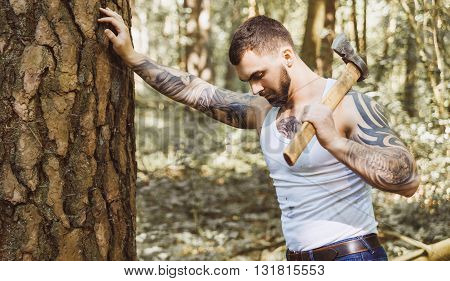 Portrait of young stylish lumberjack with axe in forest.