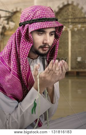 Portrait of Arabic man sitting in the mosque and praying while holding beads and wearing headscarf
