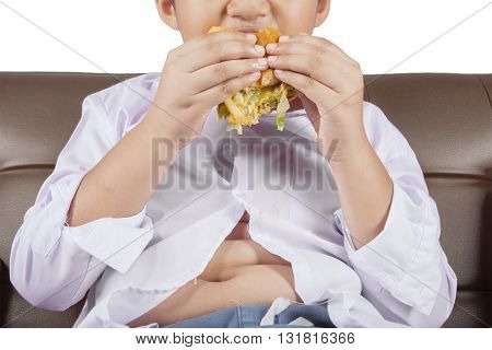 Close up of a little boy with potbelly sitting on the sofa while enjoying a delicious cheeseburger