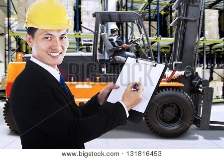 Young businessman working in the warehouse while holding a clipboard with a forklift on the background