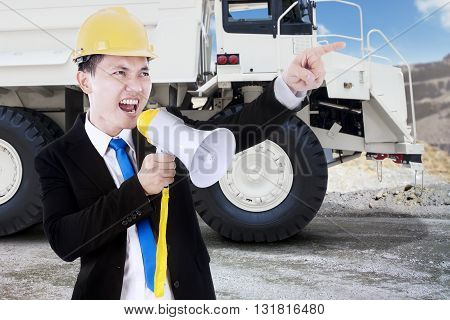 Young businessman yelling uses a megaphone in the mining site with a big truck on the background