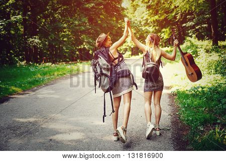 Two woman traveler walking along the road through woods