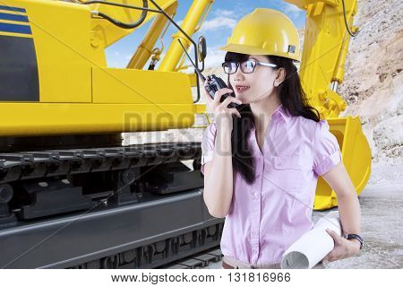 Portrait of female contractor talking on the walkie talkie with an excavator in the construction site