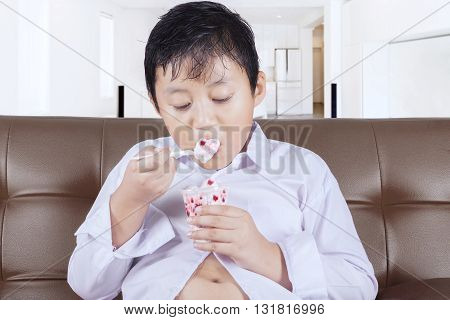 Picture of a cute boy eating ice cream while sitting on the couch at home