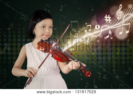 Photo of a cute little girl playing a melody with a violin on the stage