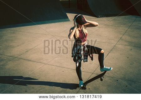 Young woman standing on a skateboard and listening to music in skate park