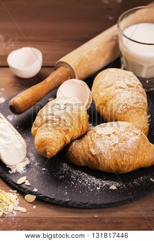 Fresh baked croissants with almond leaves on the wooden table. Selective focus
