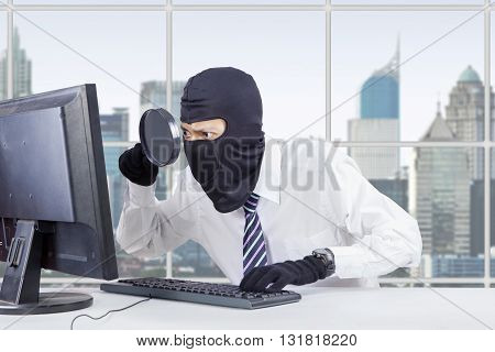 Photo of male hacker wearing mask and using magnifier to steal information on the computer in the office