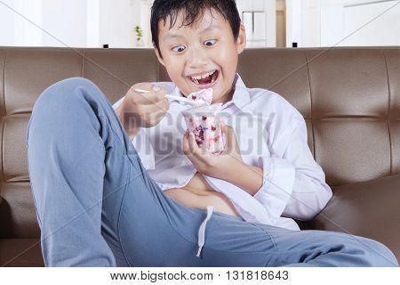 Joyful little boy sitting on the sofa while enjoying a glass of ice cream at home