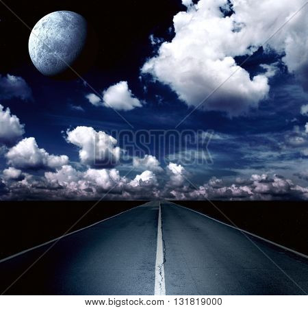 Automobile headlights illuminated the road in the field. Night landscape with road, clouds and the moon. Elements of this image furnished by NASA